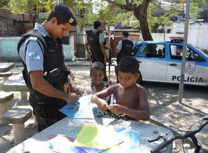 Un policía pacificador ayuda a dos niños a montar una cometa en la favela Ciudad de Dios de Río de Janeiro.