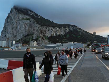 Peatones y vehículos cruzan la pista del aeropuerto de Gibraltar camino de la Verja para pasar a España.