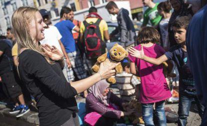 Una trabajadora de la iniciativa 'Ayuda a los Refugiados en Múnich' entrega un oso de peluche.
