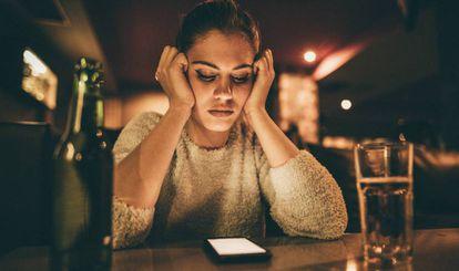 Una joven consulta su móvil conectada a una wifi gratuita.