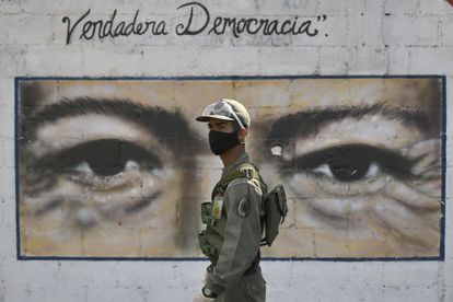 Un soldado custodia una escuela de Caracas en cuya pared tiene los ojos de Hugo Chávez, en las elecciones legislativas del 6 de diciembre pasado.