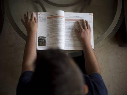 Rafael con su libro de la asignatura de Técnicas de Almacén en su casa de Córdoba.