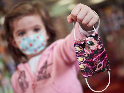 Una niña muestra una mascarilla infantil mientras sale a la calle en el primer día de relajamiento del confinamiento.