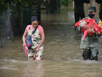 Una mujer es auxiliada en las inundaciones en Nacajuca, en Tabasco (México), por un elemento del Ejército que carga a su bebe el pasado domingo.