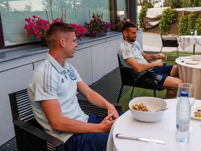 Dani Olmo y Unai Simón siguen a través de un teléfono móvil el amistoso entre España, que juega con el equipo sub 21, y Lituania, este martes en la Ciudad del Fútbol de Las Rozas, en Madrid.