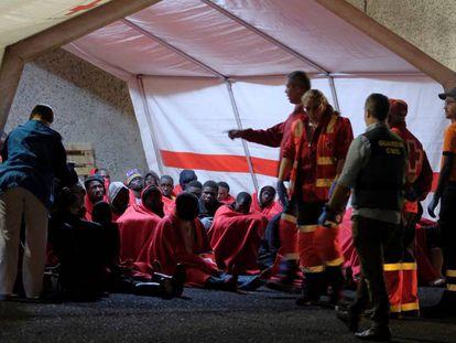 Miembros de la Cruz Roja y de la Guardia Civil atienden este jueves a un grupo de inmigrantes que ha llegado a Arguineguín (Gran Canaria).