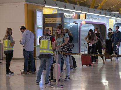 Control de seguridad en el aeropuerto de Barajas en octubre, con tiendas cerradas al fondo.