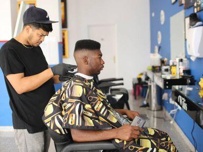 Un militar estadounidense se corta el pelo en un peluquería de Rota.