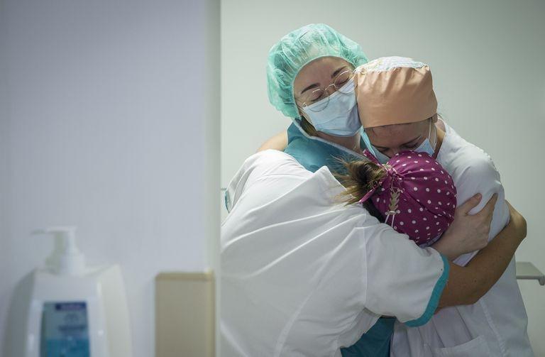 Tres enfermeras se abrazan por el traslado a planta del último paciente ingresado en la Unidad de Cuidados Intensivos con coronavirus del hospital Quirónsalud Sagrado Corazón de Sevilla.