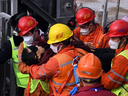 Trabajadores de los equipos de rescate ayudan a salir a uno de los mineros atrapados