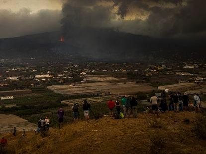 Un grupo de curiosos contempla la erupción del volcán desde La Laguna, el martes.