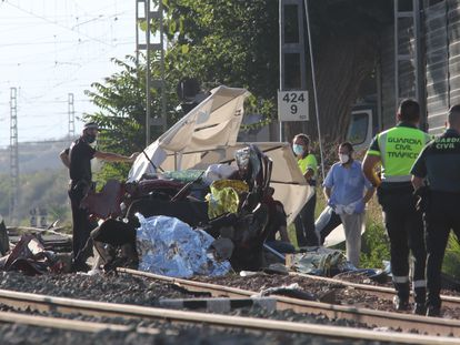 Miembros de los servicios de emergencia retiran restos del vehículo en el que cuatro personas han fallecido tras colisionar en un paso a nivel de la estación alicantina de Novelda.