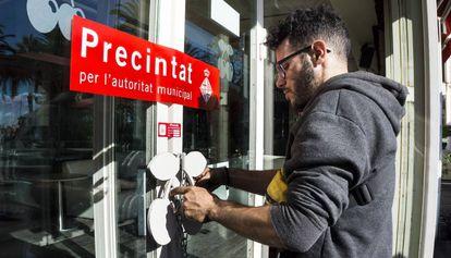 Un operario coloca una cadena en la puerta de Pacha