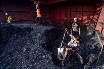 Unos trabajadores descargan carbón en Gabtoli, Bangladesh.