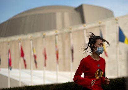 Una mujer corre con mascarilla frente al edificio de Naciones Unidas en Nueva York, Estados Unidos, este martes.