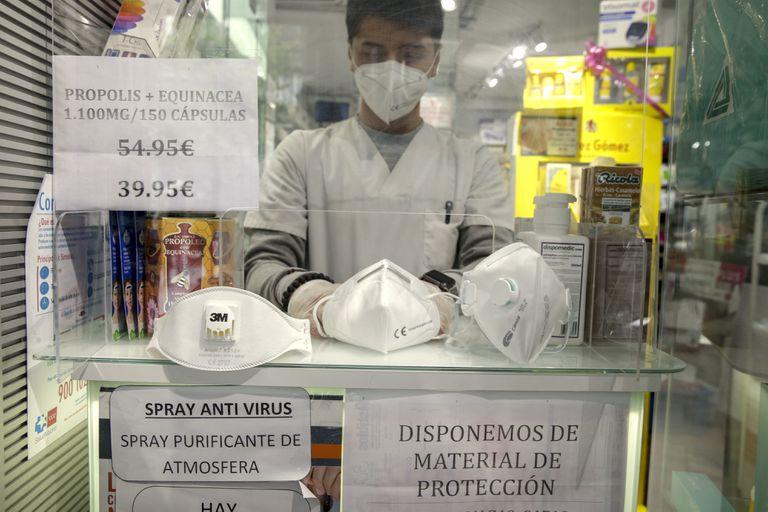 Un empleado de una farmacia despliega mascarillas FFP1, izquierda, FFP2, centro y FFP3, derecha, en una farmacia en Madrid.