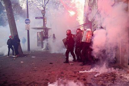 Agentes antidisturbios se enfrentan a varias personas en una calle céntrica de la capital francesa.