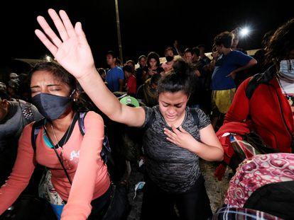 Dos mujeres hondureñas rezan antes de poner rumbo a Estados Unidos en una nueva caravana de migrantes que se formó en la noche del 9 de diciembre en San Pedro Sula.