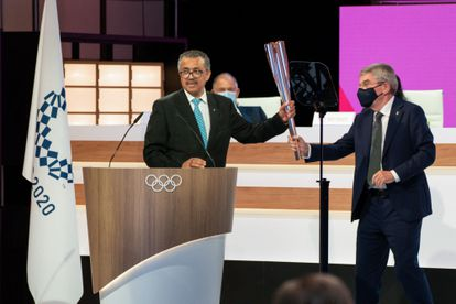 The WHO Director General, left, receives the Olympic torch from the IOC President.