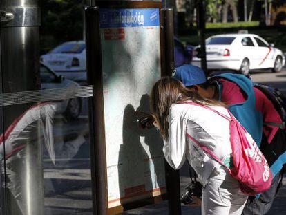 Una pareja de turistas miran un plano del metro de Madrid.