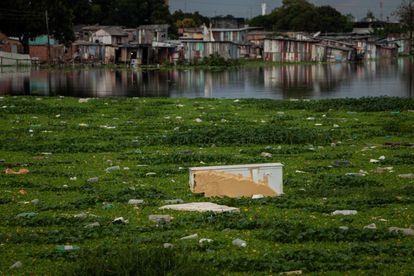 Fotografía tomada el 2 de junio de 2021, que muestra a un refrigerador que flota en las aguas de un arroyo cubierto por gran cantidad de basura, en la región sur de Manaos (Brasil).