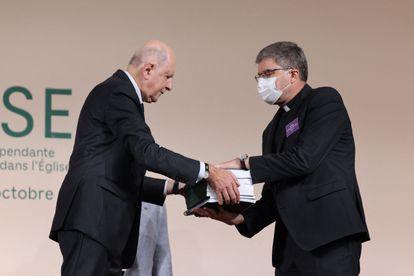 Jean-Marc Sauvé, a la izquierda, entrega copias del informe sobre pederastia al obispo Eric de Moulins-Beaufort, presidente de la Conferencia Episcopal de Francia.