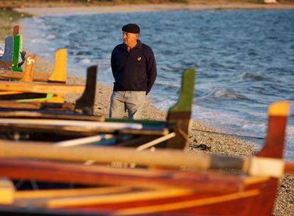Uxío Allo observa una dorna en la playa de Bao, en la Illa de Arousa.