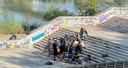 Jóvenes haciendo botellón, este sábado, en los márgenes del río Guadalquivir.
