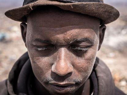 Mamadou, un reciclador de Guinea, posa para un retrato con el rostro cubierto de polvo en el basurero de Mbeubeuss, en Dakar, el 14 de julio de 2021.
