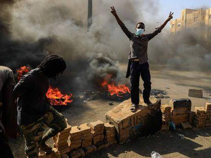 Manifestantes sudaneses queman neumáticos para bloquear una carretera de Jartum.