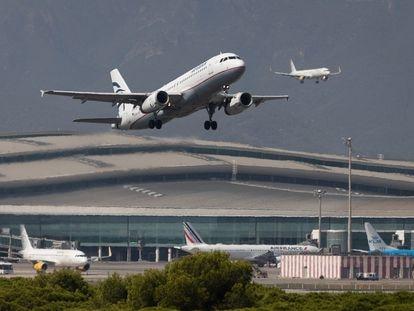 En la imagen, un avión despega mientras otro aterriza simultáneamente en el aeropuerto. / ALBERT GARCIA