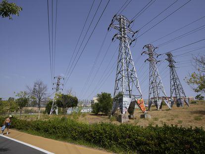 Un hombre camina junto a las torres eléctricas de una subestación eléctrica de Madrid, este miércoles.