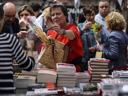 Una mujer adquiere un libro en una parada en La Rambla de Barcelona durante la festividad de Sant Jordi de 2019.