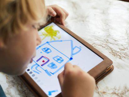 Un niño se entretiene mientras dibuja en una tableta.