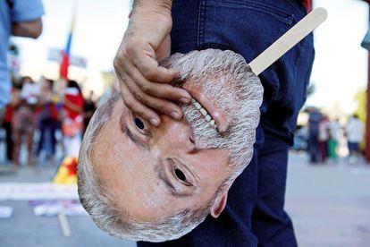 Un manifestante pasea una máscara con la cara de Lula