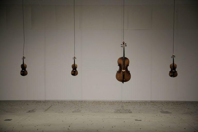 Instalación de Cabosanroque 'Sous les violons, la plage!', en el centro de arte Lo Pati de Amposta, en la que los espectadores lanzan piedras a los instrumentos.