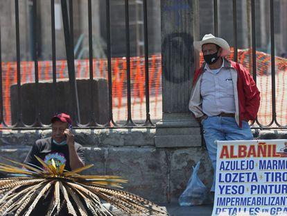 Dos hombres ofrecen sus servicios de trabajo en las rejas de la Catedral Metropolitana, el 26 de julio en Ciudad de México.