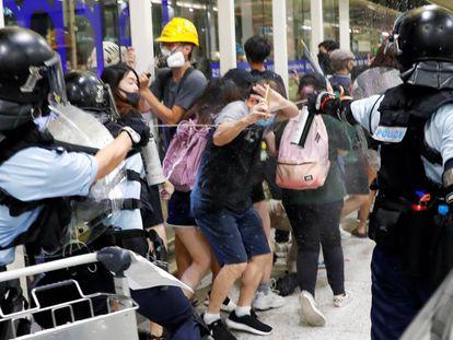 La policía rocía con gas pimienta a los manifestantes.