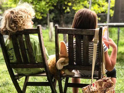 Dos niños conversan en el jardín.