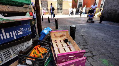 Cajas de comida en la basura en la puerta de un establecimiento, en el centro de Madrid.