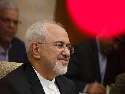 El ministro de Exteriores iraní, Mohammad Javad Zarif, este domingo en Pekín. En vídeo, un grupo de diputados iraníes quema una bandera estadounidense la semana pasada en el Parlamento.
