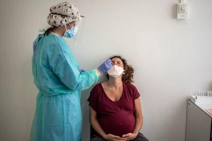 Una enfermera toma una muestra nasofaríngea a una mujer embarazada para realizarle una prueba de detección de la covid