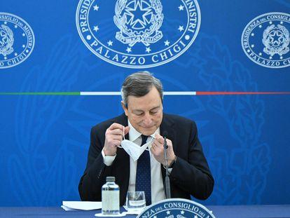 El primer ministro italiano, Mario Draghi, se retira la mascarilla para intervenir tras una reunión de su Gobierno, este viernes en Roma.
