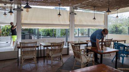 Un empleado de un restaurante limpia las mesas antes de la llegada de los clientes.