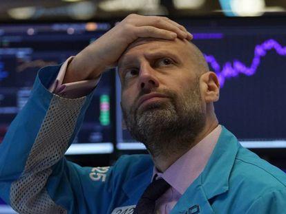 Un administrador de mercado mira las pantallas de valores en Wall Street.