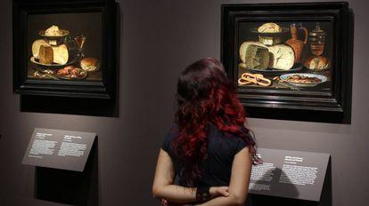 Una mujer observa dos bodegones de la pintora flamenca Clara Peeters, en una exposición en el Museo del Prado.