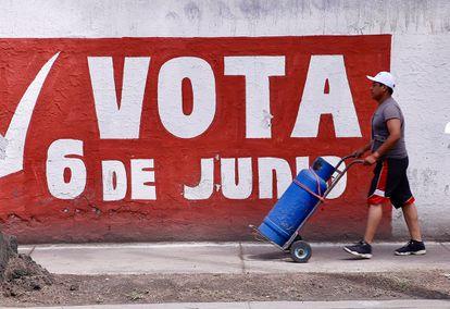 Transeúnte pasa frente a propaganda electoral en Ciudad de México. EFE/Carlos Ramírez