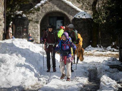 Peregrinos de origen asiático llegan a O Cebreiro cubierto de nieve.