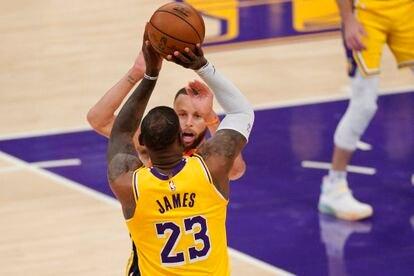 LeBron James, pese a la oposición de Curry, lanza el triple que decidió el partido entre los Lakers y los Warriors.