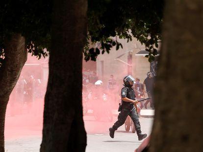 Un policía corre detrás de un grupo de manifestantes en medio de una nube de gas lacrimógeno en la capital de Túnez, el 25 de julio de 2021.